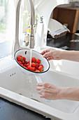 Hands washing colander of strawberries in running water