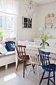 Verschiedenfarbige Windsorstühle am Tisch im ländlichen Esszimmer