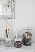 Pebbles and paintbrushes in storage jars