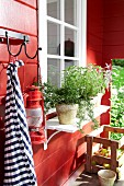 A red garden shed with culinary herbs in front of the window
