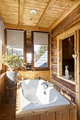 Wood-clad white bathtub below interior window in rustic dacha