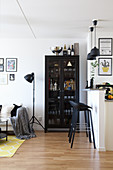 Barstools at partition kitchen counter and glasses in black glass-fronted cabinet