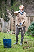 Woman removing thatch from lawn leaning on rake