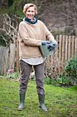 Woman holding zinc bucket in rustic garden