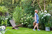 Woman, flowerbeds and lawn in garden
