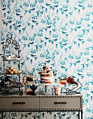 Sweet buffet on a console in front of wallpaper with bird motif