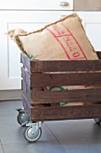 Scatter cushion in wooden crate on castors