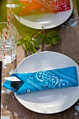 Bandanas used as napkins on rustic wooden table in garden