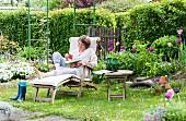 Idyllischer Schrebergarten im Frühling mit Frau auf Holzliegestuhl