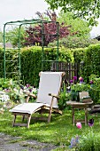 Wooden lounger, flowering tulips and trellis in garden