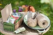 Verschiedene Samentütchen in Pappschachtel und Garn auf Gartentisch