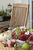 Arrangement of autumnal flowers in tureen on garden table
