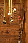 Crocheted Christmas trees in front of old wooden door and skis