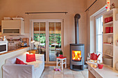 Lit fire in open-plan living room decorate in white and red
