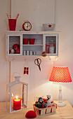 Wandschränkchen und Schreibtisch mit rot-weißer Deko