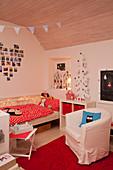 Sessel auf dem Teppich vor dem Bett im rot-weißen Kinderzimmer