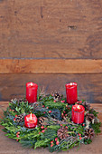 Lit red candles on Advent wreath against wooden wall