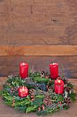 Adventskranz mit brennenden roten Kerzen vor einer Holzwand