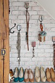 Various accessories and jewellery hung from vintage hooks on brick wall above collection of high-heeled shoes