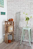 Propeller leant against brick wall between bar stool and knitted lightbulb cushion in wooden crate