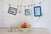 Old photos with crocheted picture frames hung from line