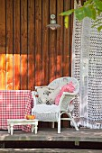 Cushions on white wicker armchair on wooden terrace
