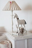 Table lamp and wooden horse on wheels on white cabinet