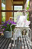 Vintage-style crockery on ornate metal table and chair on wooden deck