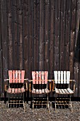 Three weathered chairs against wooden wall outdoors