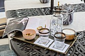 Carafe, glasses, book and candle on gilt tray