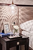 Pendant lamp casting a pattern of light and shade on wall and on bedside table