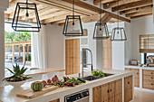 Lanterns above island counter in Mediterranean kitchen