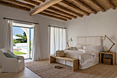 Mediterranean bedroom in natural shades with wood-beamed ceiling