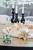 Aus buntem Papier gefaltete Origami-Sterne auf einer Schale