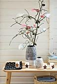 Zweig mit Zapfen und Dekovögeln in einer Vase auf Holzbank