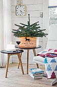 A small Christmas tree in a wooden box on a side table