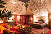 Tent style boudoir bedroom with Moroccan rugs, oriental fabrics and side table