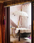 Free-standing bathtub and parasol in bathroom with patterned wallpaper and net curtains