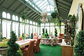 Grüner Teppich und Box Hedge Topiary in Orangerie mit Essbereich und Lounge im Hintergrund