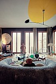 Blick vom Sofa mit Fellbezug auf bodentiefe Fenster