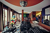 An extravagant living room with designer furniture and a disco ball