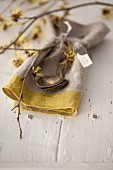 Linen napkin and cutlery decorated with flowering branches of witch hazel (Hamamelis)