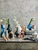 Different vases with white flowers in front of a structure wall