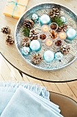 A silver bowl containing cones, blue Christmas baubles and candles