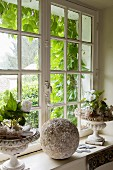 Arrangement of plants and stone ball on sill of lattice window