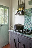 Vintage-style country-house kitchen with turquoise wall tiles and gas hob