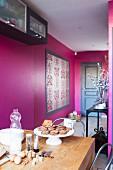 Blick von Esstisch auf pinkfarbene Wänden mit gerahmtem Brokatmuster und Eingangstür
