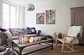 Gemütliches Wohnzimmer mit Kerzenlicht, Bogenlampe und Schaukelstuhl mit Schaffell