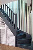 Striped wallpaper in stairwell with storage cupboards below wooden staircase