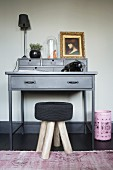 Black stool in front of vintage telephone and gilt-framed portrait of woman on grey writing desk
